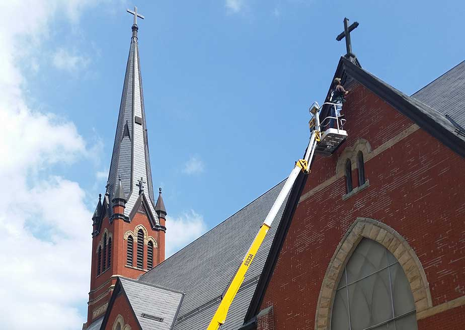Photo of man doing a bat exclusion on a very tall New York church.
